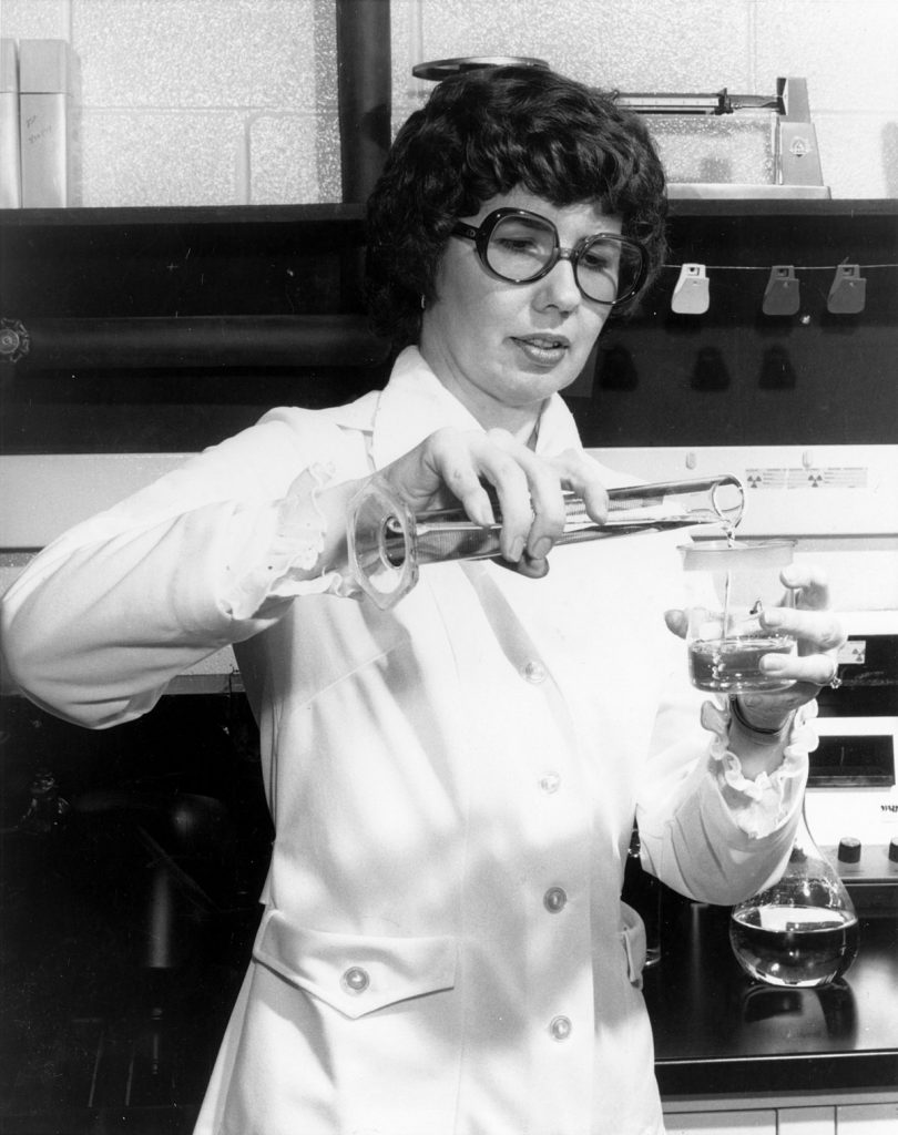 Barbara Askins pouring a liquid into a beaker wearing a white lab coat.