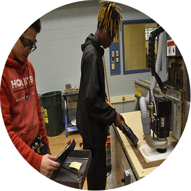 A young student cleaning up his station in carpentry with someone helping him